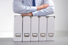 Businessman holding data files on binder shelves background Royalty Free Stock Photography