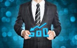Businessman holding a decreasing digital chart. Businessman in a dark suit is holding a declining chart both hands Stock Photo