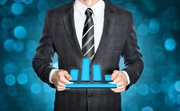 Businessman holding a digital chart symbol. Businessman in a dark suit is holding a digital chart in both hands Royalty Free Stock Photography