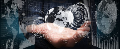 Businessman holding digital charts and globe. Businessman using futuristic screens with world and charts Royalty Free Stock Photography