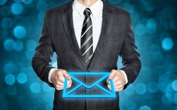 Businessman holding a digital envelope. Businessman in a dark suit is holding a digital envelope in both hands Stock Photography