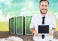 Businessman holding digital tablet against server systems in sky stock images