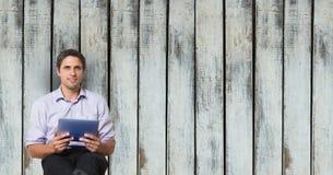 Businessman holding digital tablet against wooden wall. Digital composite of Businessman holding digital tablet against wooden wall royalty free stock photos