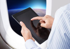 Businessman holding digital tablet in airplane Stock Image