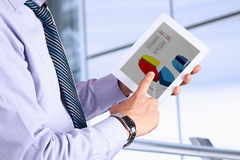 Businessman holding a  digital tablet and  analyzing financial s Stock Image