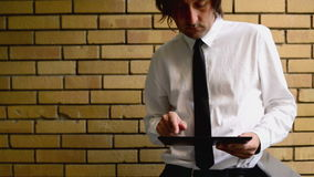 Businessman holding digital tablet computer, standing at the office balcony with yellow brick wall stock video footage