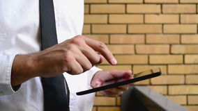 Businessman holding digital tablet computer, standing at the office balcony with yellow brick wall stock video