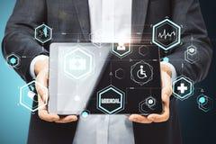 Businessman holding digital tablet with glowing medical interface hud hologram