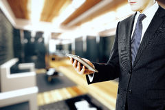 Businessman holding digital tablet in modern wood style office Stock Photography