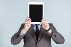 Businessman holding digital tablet over his face. Isolated on grey royalty free stock photo