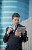 Businessman holding digital tablet standing outdoors working outdoors business district Stock Photography