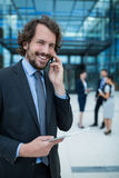 Businessman holding digital tablet talking on mobile phone Royalty Free Stock Image