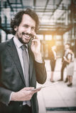 Businessman holding digital tablet talking on mobile phone. Portrait of businessman with digital tablet talking on mobile phone in office premises Stock Images