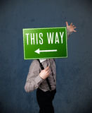 Businessman holding a direction sign Stock Photo