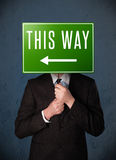 Businessman holding a direction sign Royalty Free Stock Photography