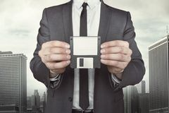 Businessman holding diskette in hands. On cityscape background Royalty Free Stock Images