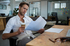 Businessman holding disposable coffee cup while reading document at desk Stock Photo