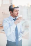 Businessman holding disposable cup and tablet looking out the window Stock Photography