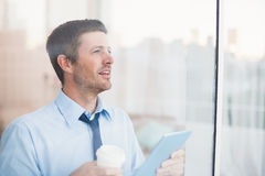 Businessman holding disposable cup and tablet looking out the window Stock Image