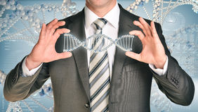 Businessman holding dna spiral in hands. Hi-tech graphs as nackdrop stock images