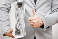 Businessman is holding document binders and showing thumbs up ge Royalty Free Stock Photo