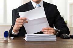 Businessman Holding Document At Desk Royalty Free Stock Photography