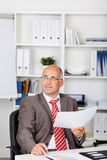 Businessman Holding Document While Looking Away Stock Images