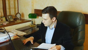Businessman holding document and typing at the laptop in the office stock video footage