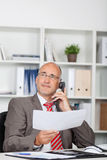Businessman Holding Document While Using Landline Phone Stock Photos