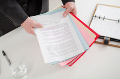 Businessman holding documents. On his desk stock photos