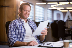 Businessman holding documents while sitting at desk Royalty Free Stock Photography