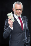 Businessman holding dollar banknotes. Handsome mature businessman holding dollar banknotes and smiling at camera Stock Photo