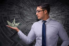 The businessman holding dollar paper boats Stock Image