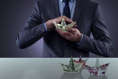 The businessman holding dollar paper boats Royalty Free Stock Image
