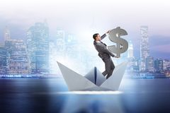The businessman holding dollar riding paper ship boat Royalty Free Stock Image