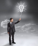 Businessman holding a drawing of a light bulb Stock Photography