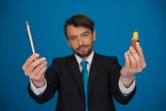 Businessman holding e-cigarette and e-liquid on blue Stock Photo