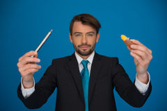 Businessman holding e-cigarette and e-liquid on blue Royalty Free Stock Photography