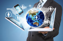 Businessman holding earth and electronics Royalty Free Stock Images