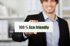 Businessman Holding Eco Friendly Sign. Portrait of handsome young businessman holding Eco Friendly sign in office Stock Photography