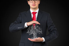 Businessman holding electronics tree Royalty Free Stock Photos