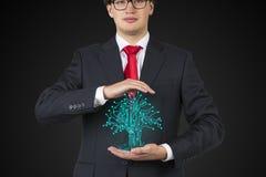Businessman holding electronics tree Stock Photo
