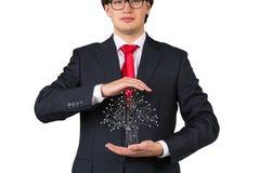 Businessman holding electronics tree Royalty Free Stock Photos