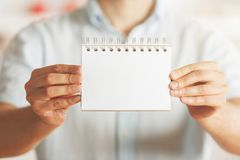Businessman holding empty notepad. Businessman holding empty spiral notepad on blurry interior background. Mock up and presentation concept Royalty Free Stock Image
