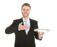 Businessman holding empty tray over white background Stock Photos