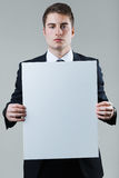 Businessman holding empty white placard showing copy space. Stock Image