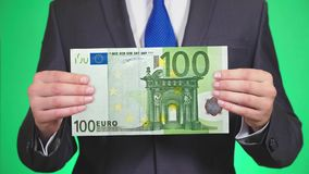 Businessman holding a euro bill in his hand., green background, close-up, slow motion. space for copying stock video