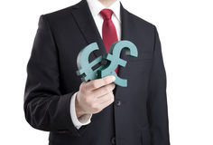 Businessman holding euro and pound signs Royalty Free Stock Photography