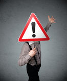 Businessman holding an exclamation road sign Stock Image