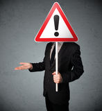 Businessman holding an exclamation road sign Royalty Free Stock Photography